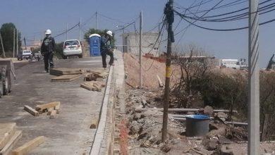 Photo of Caen dos trabajadores de un poste de concreto